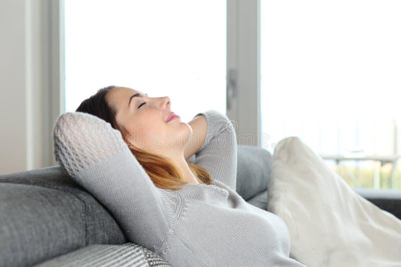 Lycklig avkopplad kvinna som hemma vilar på en soffa royaltyfria foton