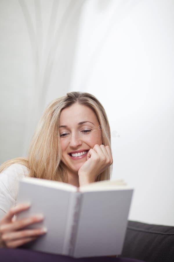 Lycklig avkopplad kvinna som läser en bok royaltyfri fotografi