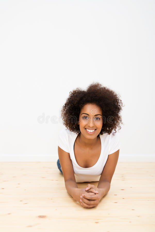 Lycklig avkopplad kvinna som ligger på ett trägolv fotografering för bildbyråer
