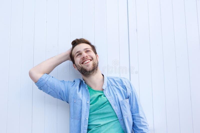 Lycklig avkopplad man som ler med handen i hår arkivbild