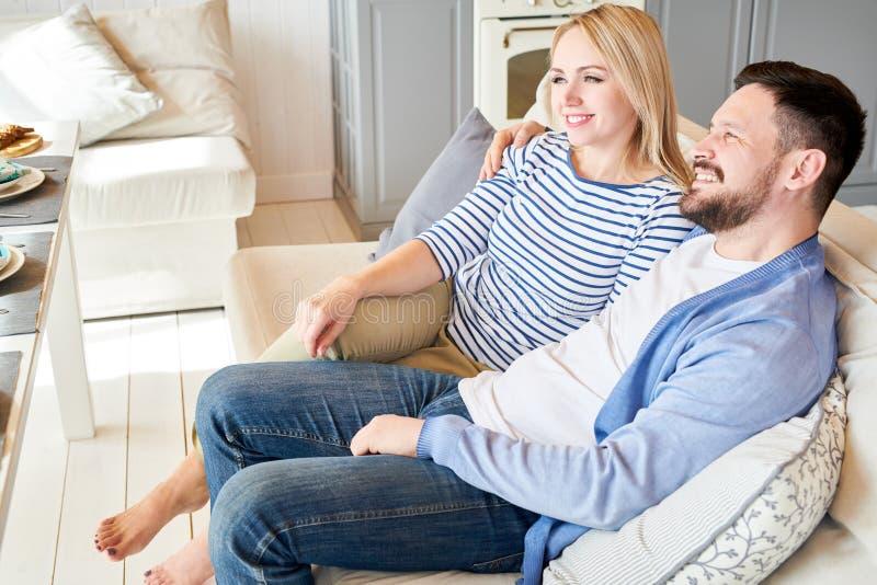 lycklig avslappnande sofa för par royaltyfri bild
