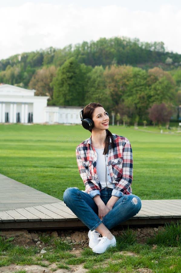Lycklig avslappnande yttersida för ung kvinna, medan sitta på trägränden arkivbild