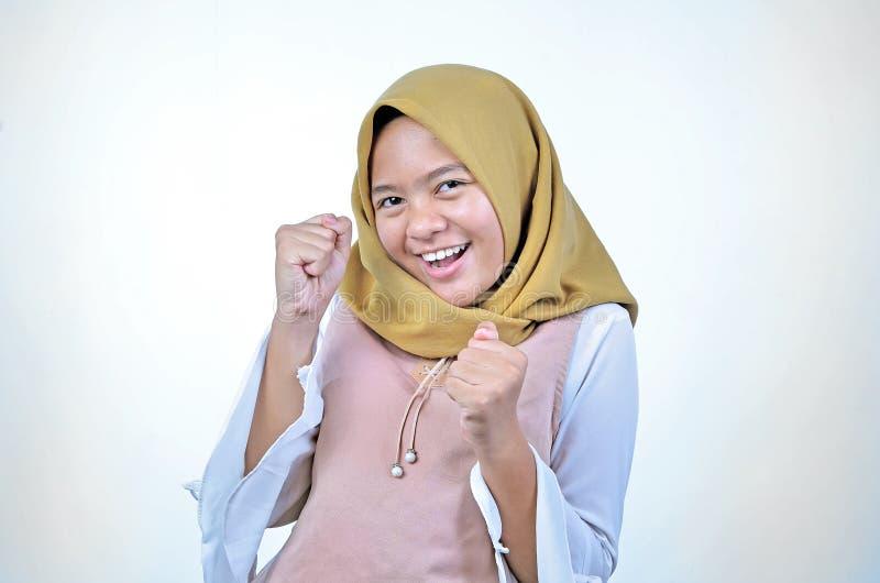 Lycklig bärande hijab för asiatisk kvinna och upphetsad fira seger som uttrycker stor framgång, makt, energi och positiva sinnesr royaltyfria foton
