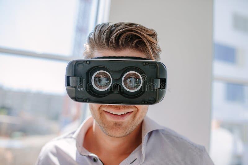Lycklig bärande virtuell verklighet för den unga mannen rullar med ögonen royaltyfria foton