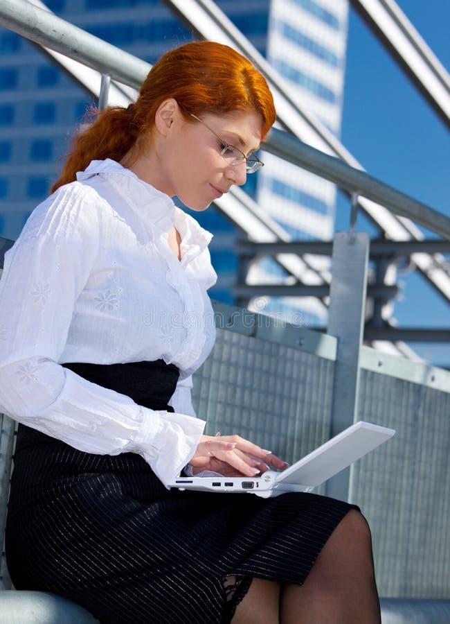 lycklig bärbar dator för affärskvinnastad royaltyfria bilder
