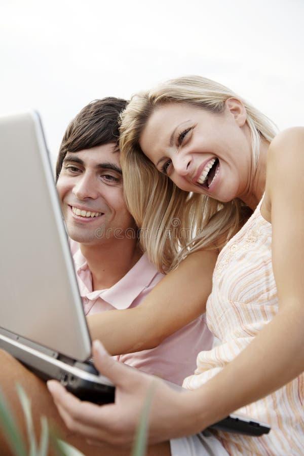 lycklig bärbar dator för par arkivbild