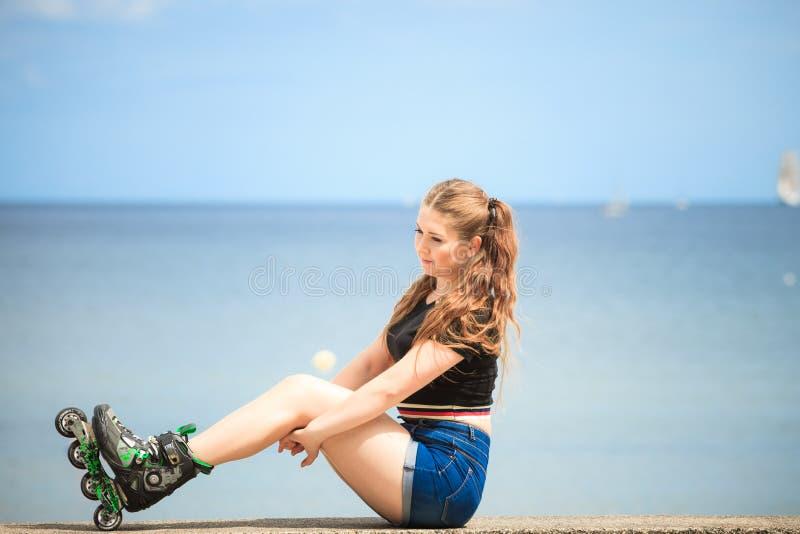 Lycklig b?rande rullskridskor f?r ung kvinna royaltyfria foton