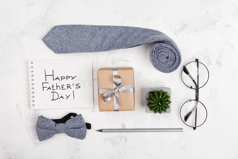 Lycklig bakgrund för faderdag med anteckningsboken, gåvan, exponeringsglas, slipsen och bowtie på ljus funktionsduglig skrivbords fotografering för bildbyråer