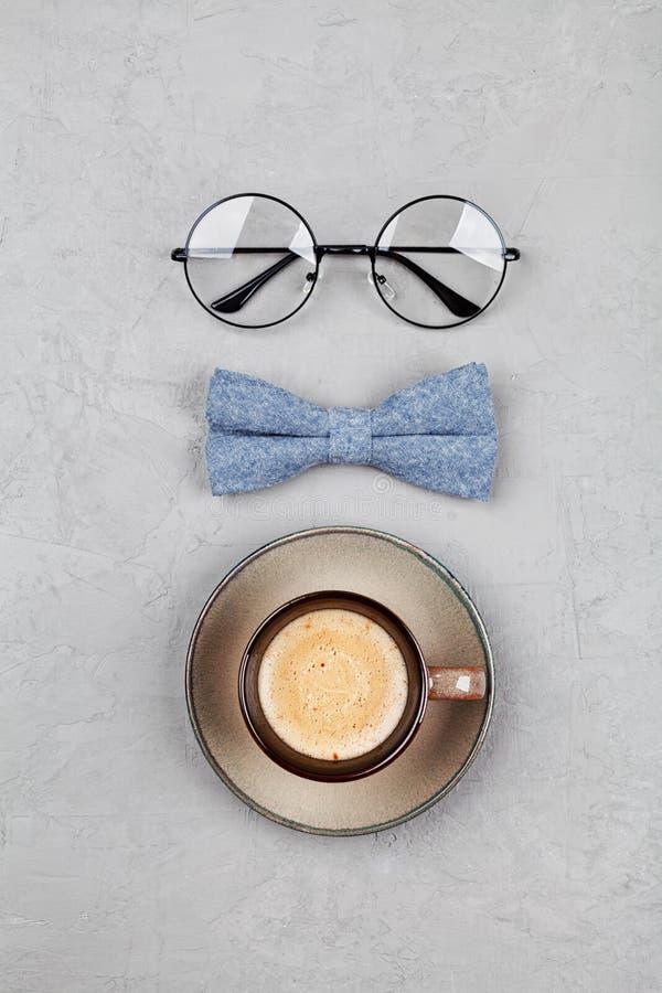 Lycklig bakgrund för faderdagen med morgonkaffe rånar, exponeringsglas och bowtie på bästa sikt för stengrå färgtabell i lekmanna royaltyfria bilder