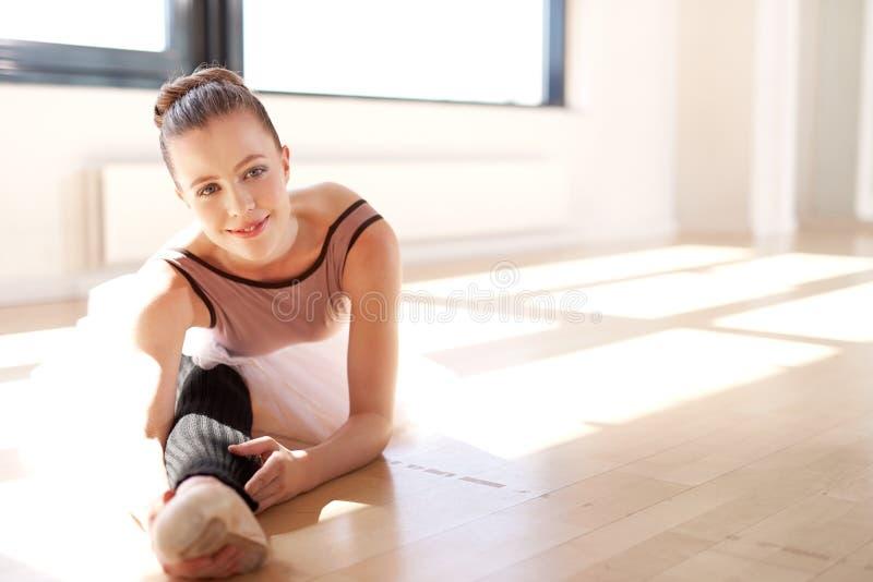 Lycklig ballerina som sträcker henne ben för uppvärmning royaltyfria bilder