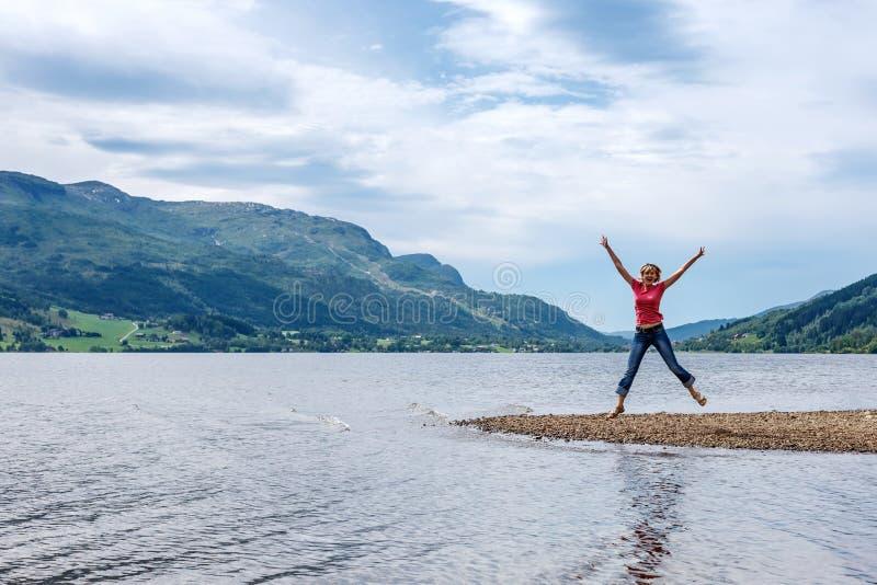 Lycklig banhoppning för ung kvinna för glädje fotografering för bildbyråer