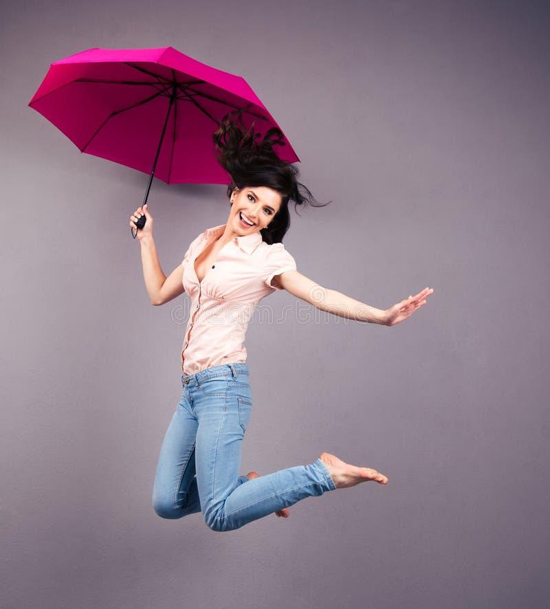Lycklig banhoppning för ung kvinna med paraplyet royaltyfri bild