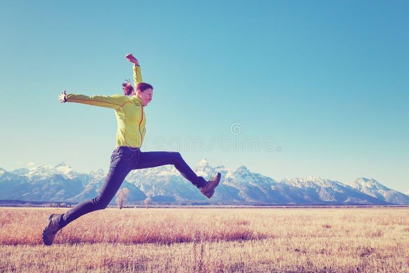 Lycklig banhoppning för ung kvinna på en bergäng arkivfoto