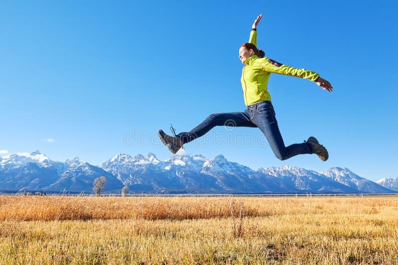 Lycklig banhoppning för ung kvinna på en bergäng royaltyfri fotografi