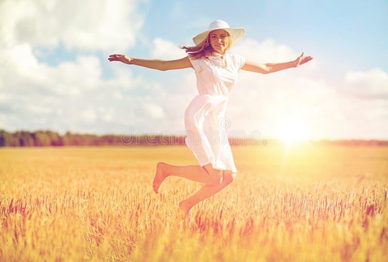 Lycklig banhoppning för ung kvinna på sädes- fält arkivfoton