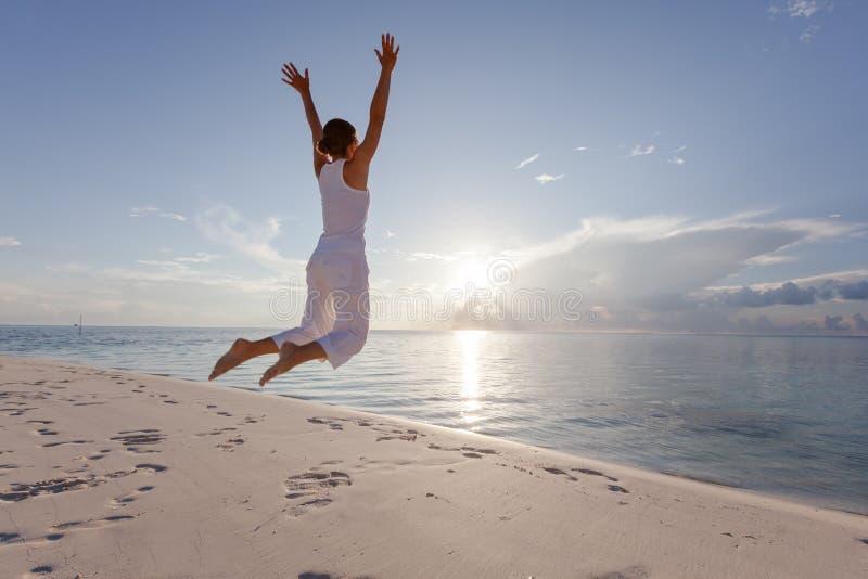 Lycklig banhoppning för ung kvinna på stranden fotografering för bildbyråer