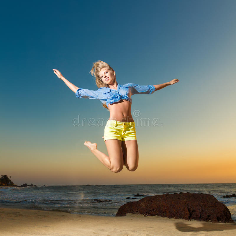 Lycklig banhoppning för ung kvinna på stranden royaltyfria bilder