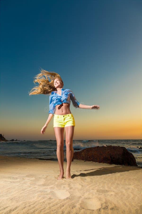 Lycklig banhoppning för ung kvinna på stranden royaltyfria foton