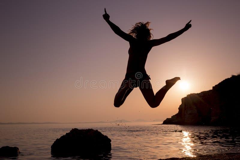 Lycklig banhoppning för ung kvinna på stranden på solnedgången royaltyfri fotografi