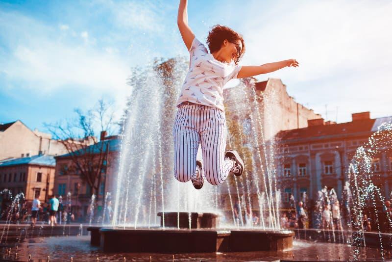 Lycklig banhoppning för ung kvinna vid springbrunnen på sommargatan royaltyfria bilder