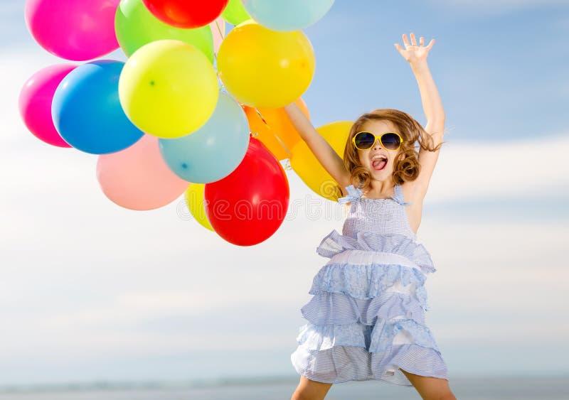 Lycklig banhoppningflicka med färgrika ballonger royaltyfri fotografi