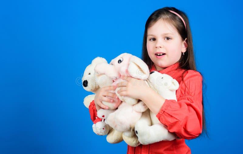 lycklig barndom Liten flickalek med den mjuka leksaknallebj?rnen Lott av leksaker i hennes h?nder Samla leksakerhobby cherishing arkivfoton