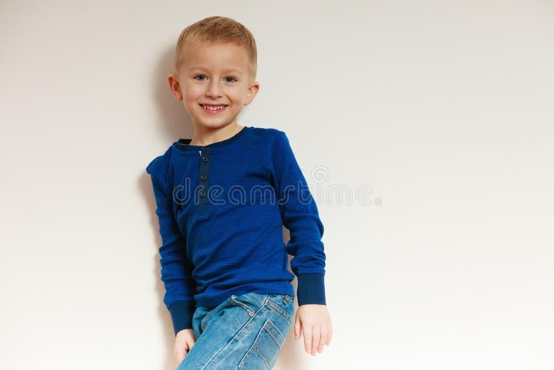 Lycklig barndom. Stående av att le den blonda pojkebarnungen inomhus arkivbilder