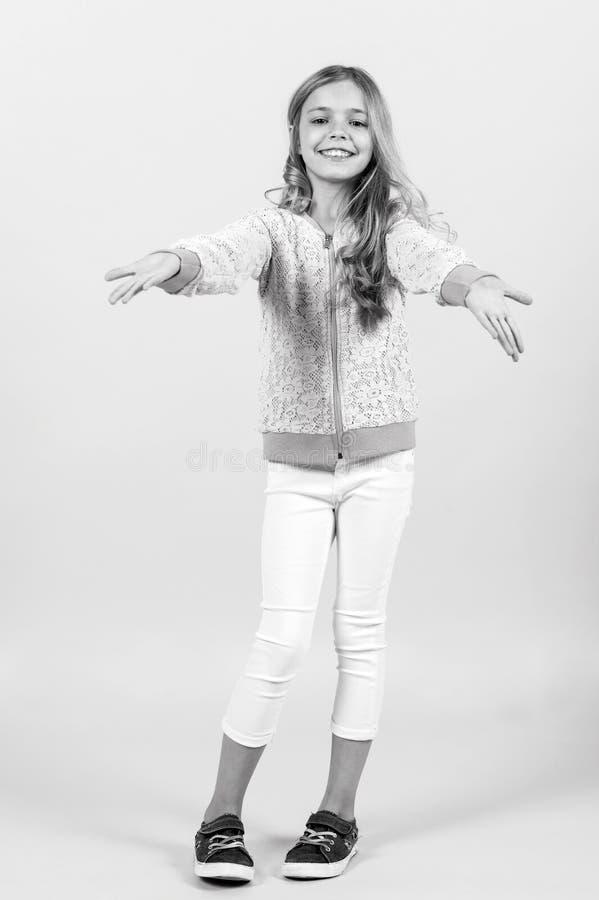Lycklig barndom, ungdom Litet flickaleende i tröjan, flåsanden, gymnastikskor, mode Barn som ler med långt blont hår fotografering för bildbyråer