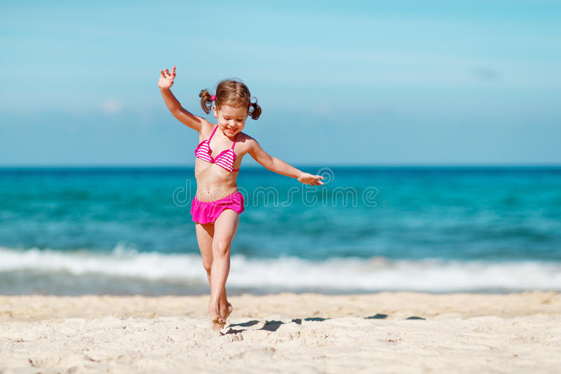 Lycklig barnflicka i bikinispring på stranden i sommarhavet fotografering för bildbyråer