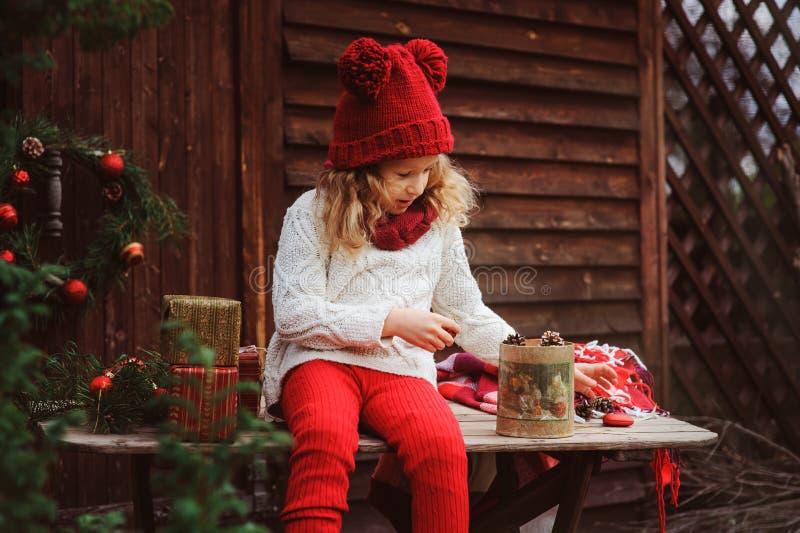 Lycklig barnflicka i röd hatt och halsduken som slår in julgåvor på det hemtrevliga landshuset som dekoreras för nytt år och jul royaltyfri fotografi
