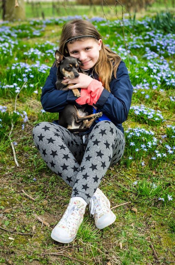 Lycklig barnflicka med den lilla hunden arkivbild