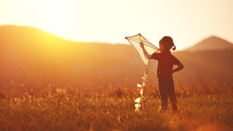 Lycklig barnflicka med en drake på äng i sommar arkivbild
