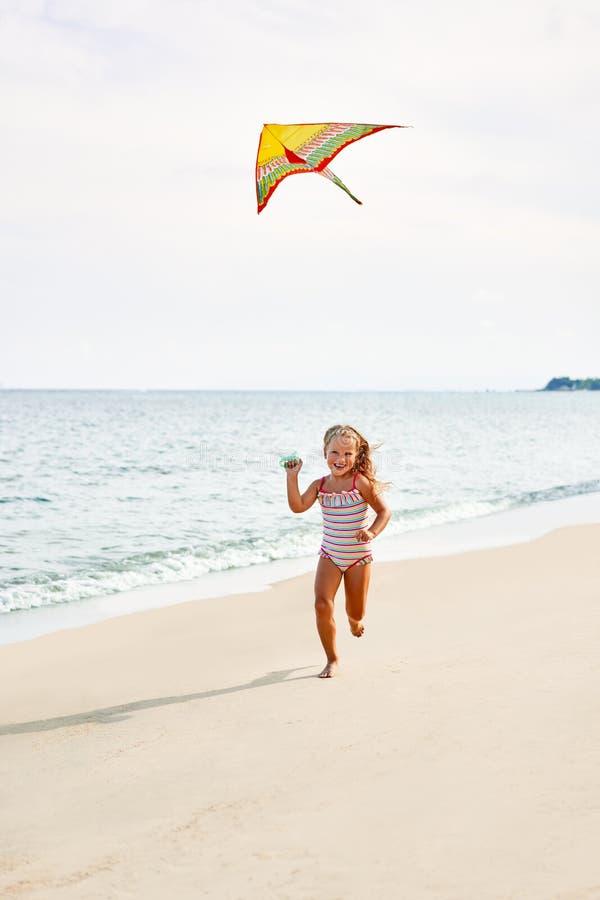 Lycklig barnflicka med en drake som kör på den tropiska stranden royaltyfri bild