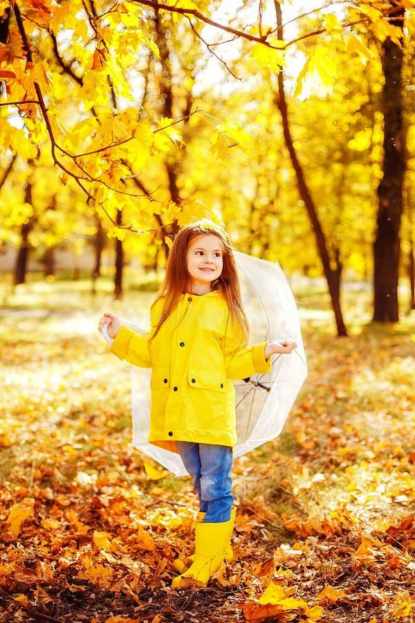 Lycklig barnflicka med ett paraply och gummistöveler som en höst går royaltyfria bilder