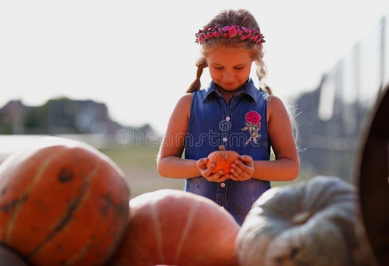Lycklig barnflicka med liten pumpa utomhus arkivfoton