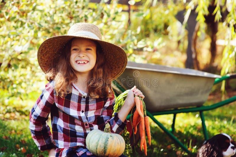 Lycklig barnflicka med spanielhunden som spelar den lilla bonden i höstträdgård och väljer grönsakskörden royaltyfri foto