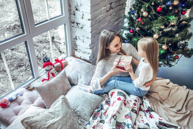 Lycklig barnflicka nära en julgran med julklapp som köps från att shoppa försäljning Xmas-ferie som överför gåvan royaltyfri foto