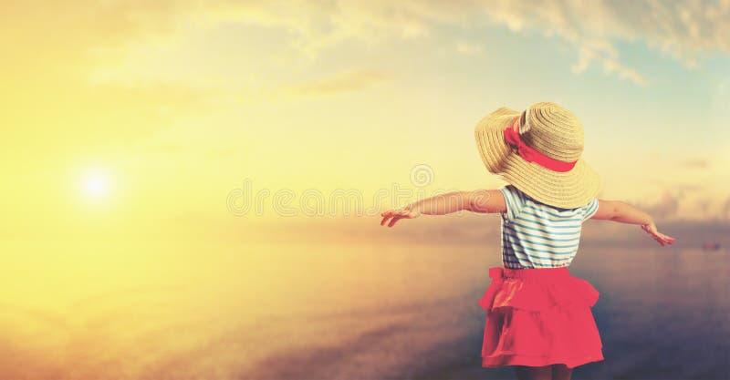 Lycklig barnflicka som beundrar solnedgång på stranden royaltyfria foton