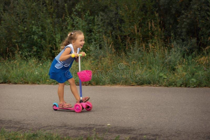 Lycklig barnflicka som rider en sparkcykel i sommaren på vägen arkivbilder