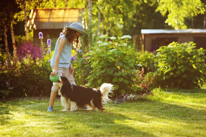 Lycklig barnflicka som spelar med hennes spanielhund och kastar bollen royaltyfri bild