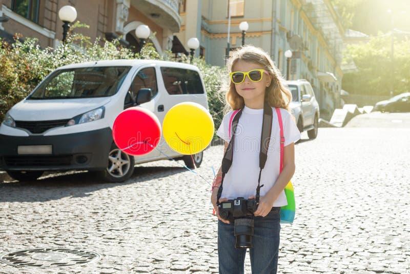 Lycklig barnflickaturist med en kamera, ballonger, en ryggsäck, arkivfoton