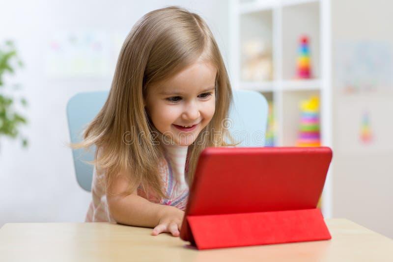 Lycklig barnliten flicka som använder minnestavladatoren royaltyfri bild
