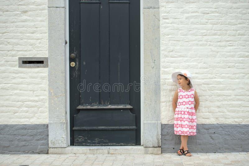 Lycklig barnliten flicka som skrattar på en tom tom netxt för tegelstenvägg till en grön dörr royaltyfri bild
