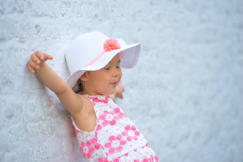 Lycklig barnliten flicka som skrattar på en tom tom tegelstenvägg fotografering för bildbyråer