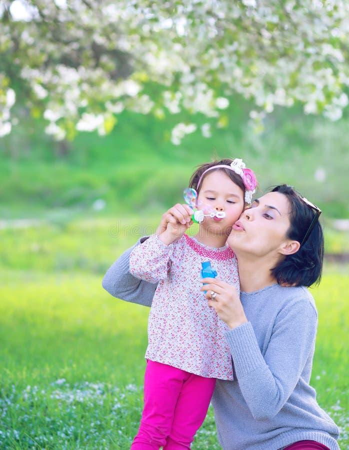 Lycklig barnmoder och hennes dotter som blåser såpbubblor royaltyfri fotografi