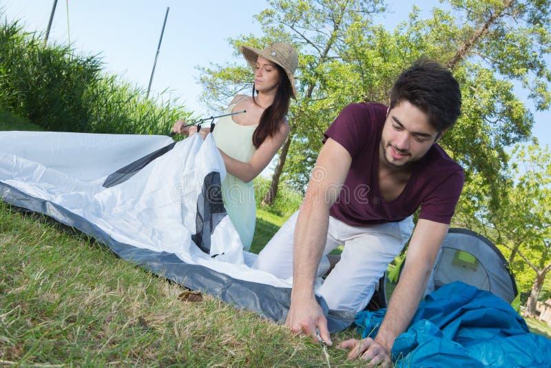 Lycklig barnparinställning - upp deras tält på den campa platsen royaltyfri foto