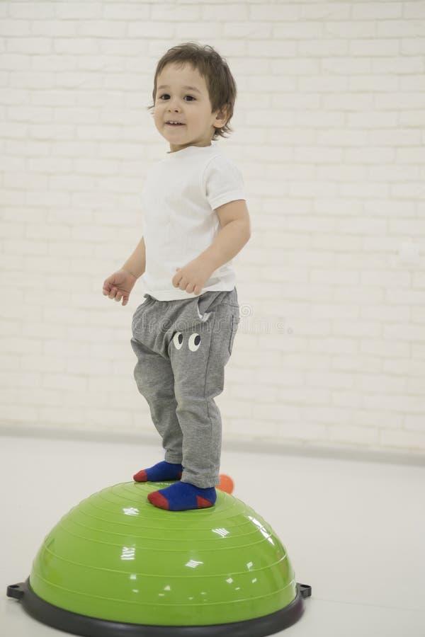 Lycklig barnpojkebanhoppning på att studsa bollen arkivbilder