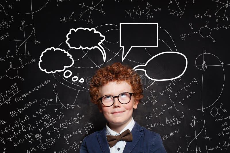 Lycklig barnstudent med formler för för anförandebubblamoln och vetenskap royaltyfri foto