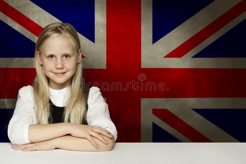 Lycklig barnstudent som sitter i klassrum mot UK-flaggabakgrunden L?r begreppet f?r det engelska spr?ket royaltyfri bild