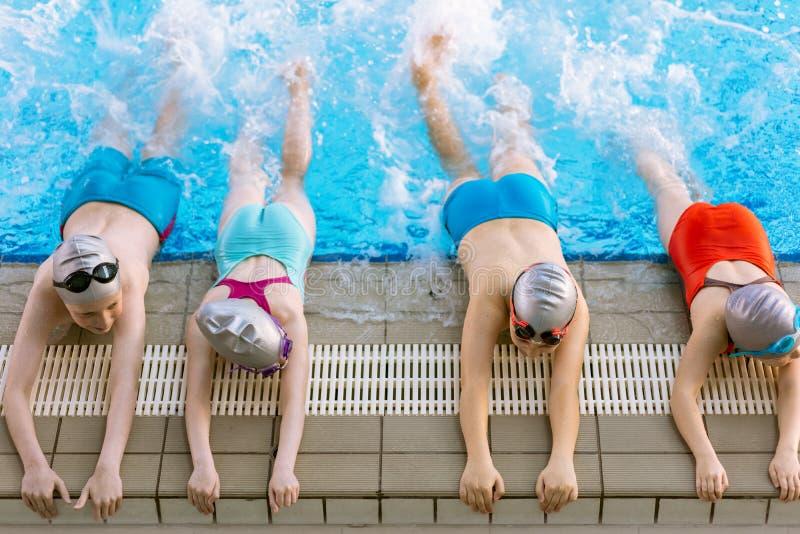 Lycklig barnungegrupp på simbassänggrupp som lär att simma royaltyfri fotografi